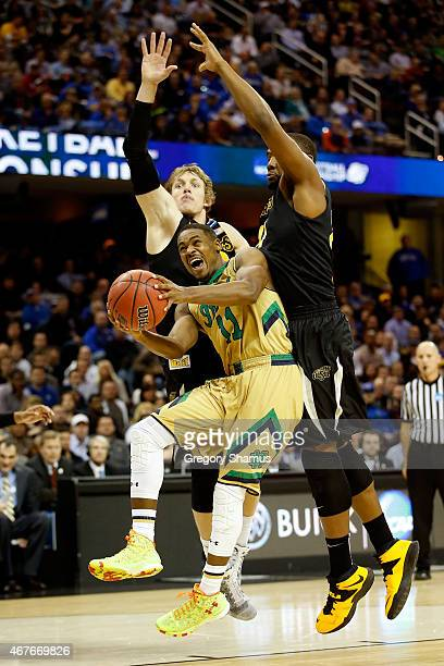 Demetrius Jackson of the Notre Dame Fighting Irish drives to the basket against Ron Baker and Shaquille Morris of the Wichita State Shockers in the...