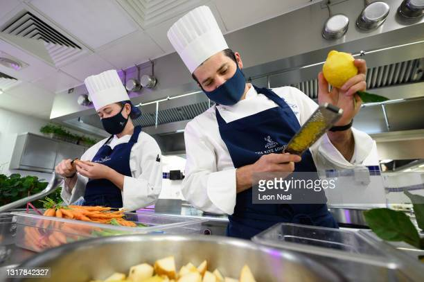 Demi Chef de Partie Megan Coape-Arnold and Premier Sous Chef Spencer Metzger prepare ingredients in the kitchens at The Ritz London on May 13, 2021...
