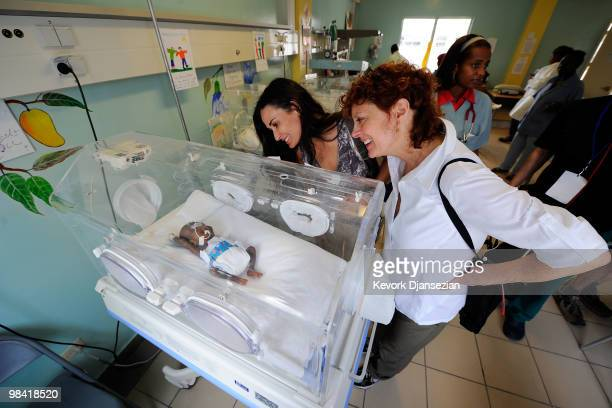 Demi Moore and Susan Sarandon look at babies in the neonatal ward of St Damien�s children's hospital on April 12 2010 in PortauPrince Haiti Moore is...