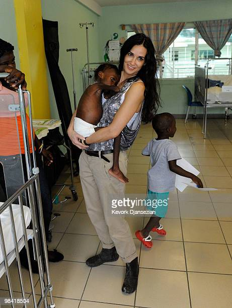 Demi Moore holds Shakyna who is suffering from malnutrition as Davidosn runs around her during the visit to the pedeatric malnutrition ward of St...
