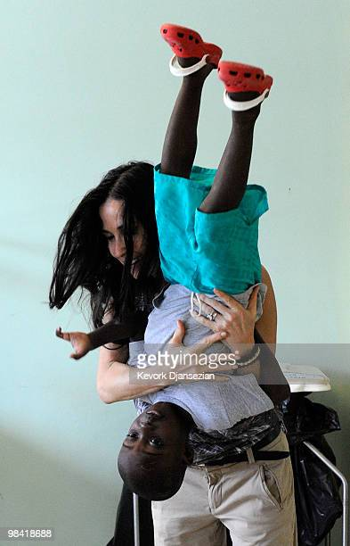 Demi Moore plays with Davidosn who lost two fingers on his left hand dur to the Haiti earthquake during her visit to the pedeatric malnutrition ward...