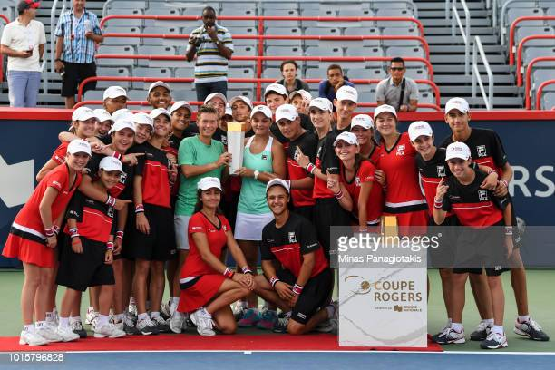 Demi Schuurs of the Netherlands and Ashleigh Barty of Australia pose with a group of ball boys and girls after defeating Latisha Chan of Chinese...