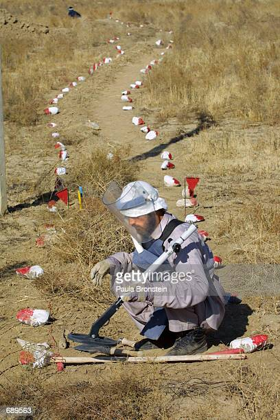 Deminer from Halo Trust uses a metal detector to search for mines January 2, 2002 on the road to Bagram, a former front line area in Afghanistan. The...