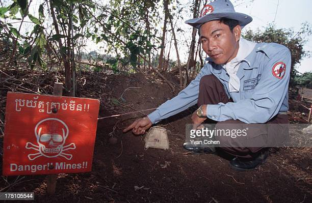 De-miner from the Cambodian Mine Action Center shows off an unexploded bomb with a danger sign beside it. Millions of anti-personnel mines still...