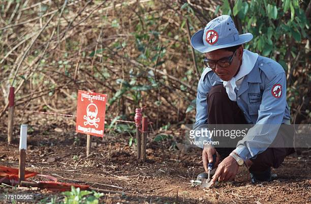 De-miner from the Cambodian Mine Action Center uses a trowel to gentle scrape the earth as he searches for mines. Beside him is a danger sign warning...