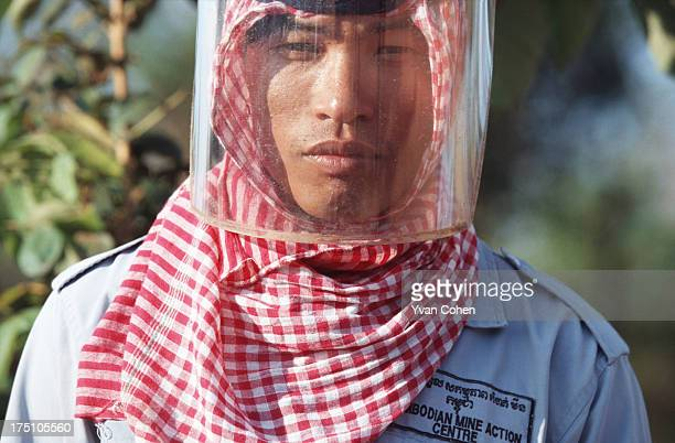 De-miner from the Cambodian Mine Action Center wears his safety visor over the top of a traditional Cambodian krama head scarf. Millions of...