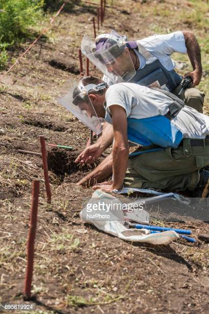 Deminers of HALO Trust organisation dig to extract a landmine in the hills of Nagorno Karabakh, on 13 June 2017. Mines still remain after 25 years...