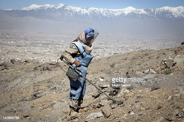 Demining engineer searches for mines across a hillside on April 07, 2012 to the south of Kabul, Afghanistan. Afghanistan's mine problem results from...