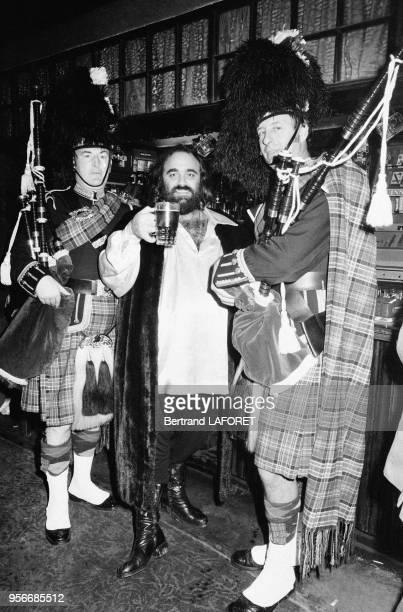 Demis Roussos à la sortie d'un pub avec deux joueurs de cornemuse à Londres le 10 novembre 1978 RoyaumeUni