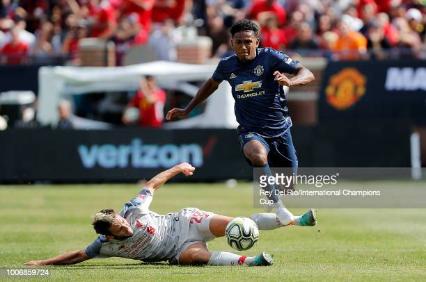Demitri Mitchell of Manchester United moves the ball past Adam Lallana of Liverpool in the first half during the International Champions Cup 2018...