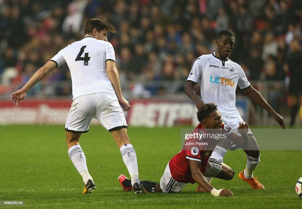 Demitri Mitchell of Manchester United U23s is fouled by Adnan Maric of Swansea City and wins a penalty during the Premier League 2 match between Manchester United U23s and Swansea City U23s at Leigh Sports Village on August 21, 2017 in Leigh, Greater Manchester.