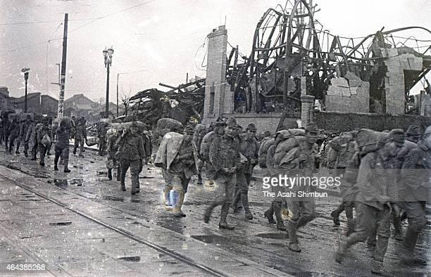 Demobilised Japanese soldiers walk among debris circa 1945 in Fukuoka, Japan.