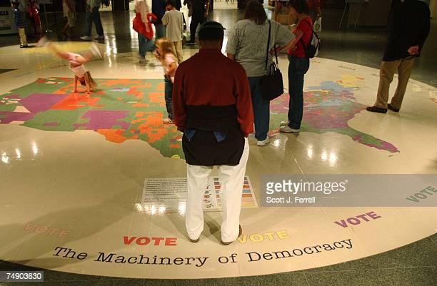 Visitors examine a United States map that shows types of voting equipment expected to be used across the nation in November's elections. The map is...