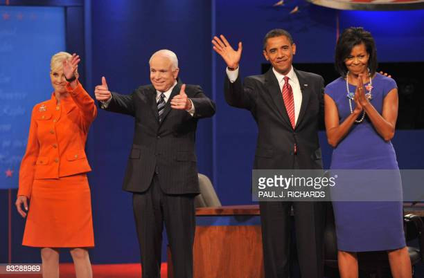 Democrat Barack Obama with wife Michelle waves to the audience as Republican John McCain flanked by wife Cindy gives the thumbsup at Hofstra...