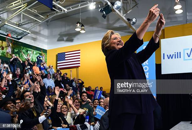 Democrat presidential nominee Hillary Clinton takes a selfie with attendees at a rally at Wayne State University in Detroit Michigan October 10 2016...