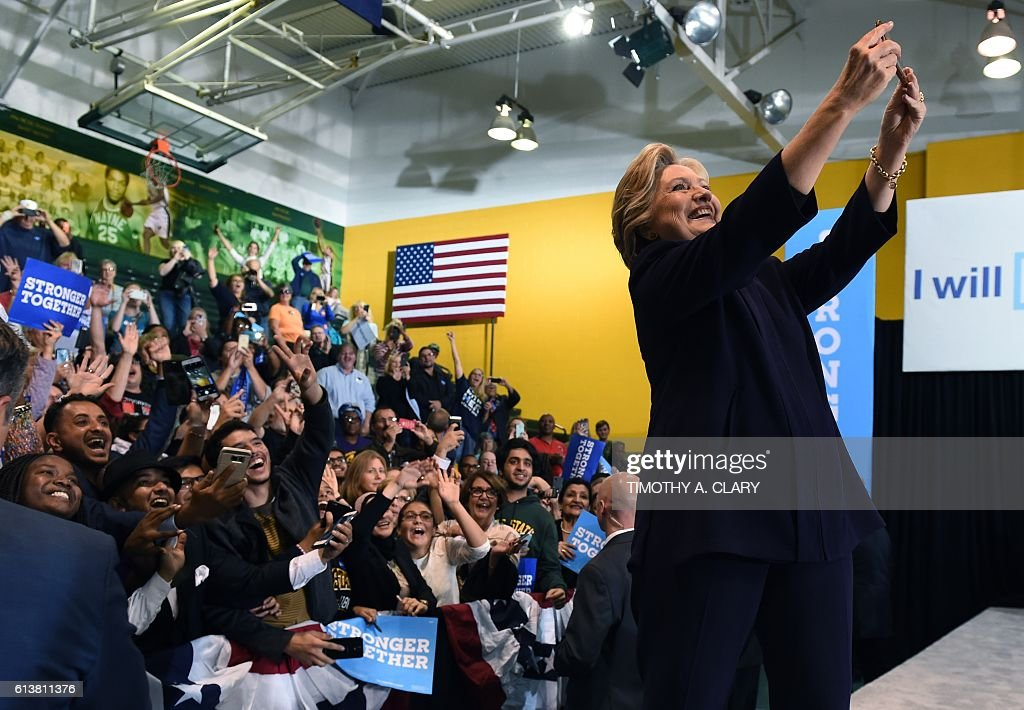 Democrat presidential nominee Hillary Clinton takes a selfie with attendees at a rally at Wayne State University in Detroit, Michigan October 10, 2016. / AFP / TIMOTHY