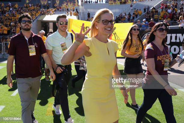Democrat US Senate candidate Kyrsten Sinema gestures on the field before the game between the Utah Utes and the Arizona State Sun Devils at Sun Devil...