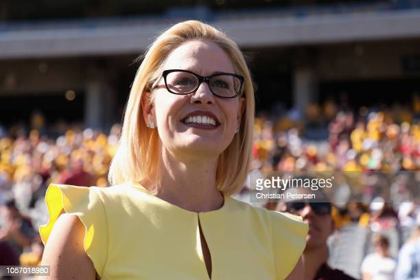 Democrat US Senate candidate Kyrsten Sinema participates in the pregame coin toss before the game between the Utah Utes and the Arizona State Sun...
