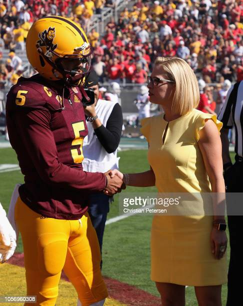 Democrat US Senate candidate Kyrsten Sinema shakes hands with quarterback Manny Wilkins as she participates in the pregame coin toss before the game...