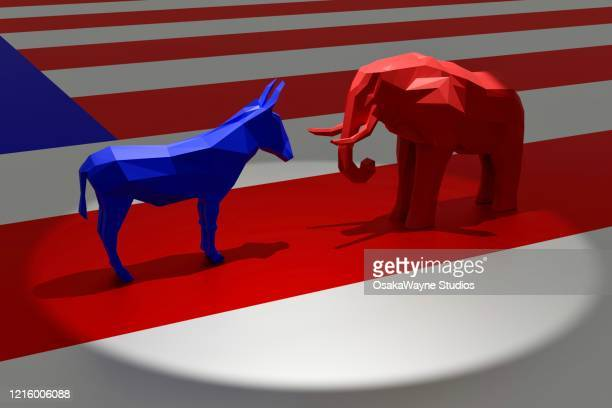 democratic blue donkey and republican red elephant in spotlight on top of american flag - democratic party usa stock pictures, royalty-free photos & images