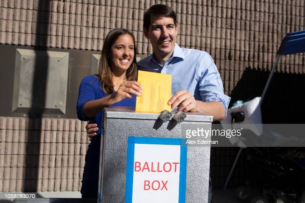 Democratic candidate for California's 10th Congressional District Josh Harder and his wife Pam Harder place Pam's ballot inside a ballot box at a...