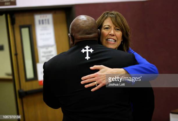 Democratic candidate for Iowa's 3rd Congressional District Cindy Axne receives a hug as she attends a Get Out the Vote rally at Corinthian Baptist...