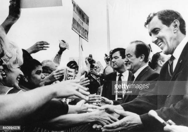 Democratic candidate for President US Vice President Hubert Humphrey and and his running mate Senator Edmund Muskie shake hands with supporters as...