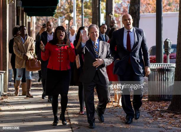 Democratic candidate for Senate Doug Jones center accompanied by Sen Cory Booker DNJ right and Rep Terri Sewell DAla left waves to supporters as he...
