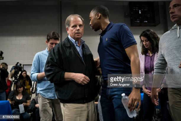 Democratic candidate for US Senate Doug Jones confers with an aide after taking questions from reporters at a fish fry campaign event at Ensley Park...