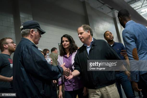 Democratic candidate for US Senate Doug Jones greets supporters before speaking at a fish fry campaign event at Ensley Park November 18 2017 in...