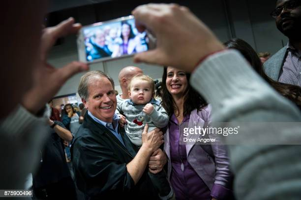 Democratic candidate for US Senate Doug Jones poses for a photo with a baby after speaking at a fish fry campaign event at Ensley Park November 18...