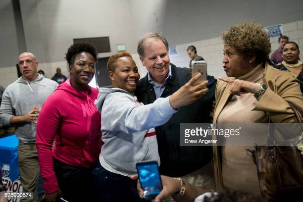 Democratic candidate for US Senate Doug Jones takes photos with supporters before speaking at a fish fry campaign event at Ensley Park November 18...