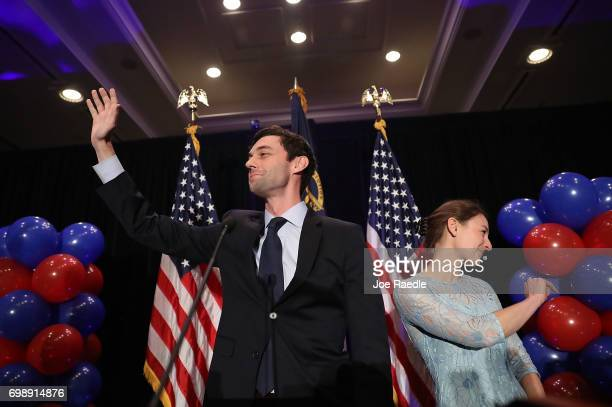 Democratic candidate Jon Ossoff and and his fiancee Alisha Kramer wave as he arrives to give a concession speech speak during his election night...