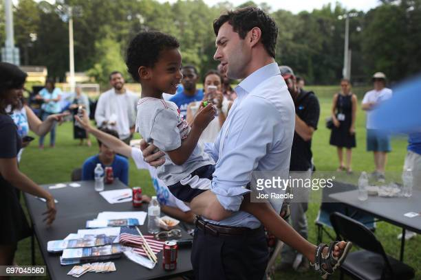 Democratic candidate Jon Ossoff holds Miles Mideau during a meet and greet with voters at a cookout as he runs for Georgia's 6th Congressional...