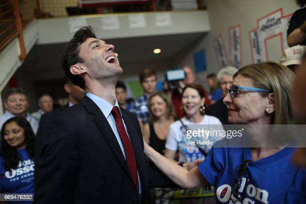 Democratic candidate Jon Ossoff laughs as he interacts with supporters during a visit to a campaign office as he runs for Georgia's 6th Congressional...
