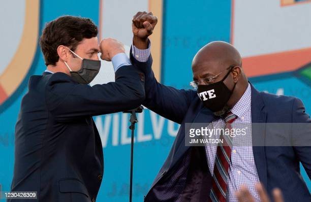 Democratic candidates for Senate Jon Ossoff and Raphael Warnock bump elbows on stage during a rally with US President-elect Joe Biden outside Center...