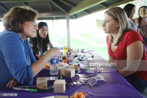 Democratic congressional candidate Katie Hill R speaks with supporter Jill Zimmerman at a campaign Halloween carnival on October 21 2018 in Lancaster...