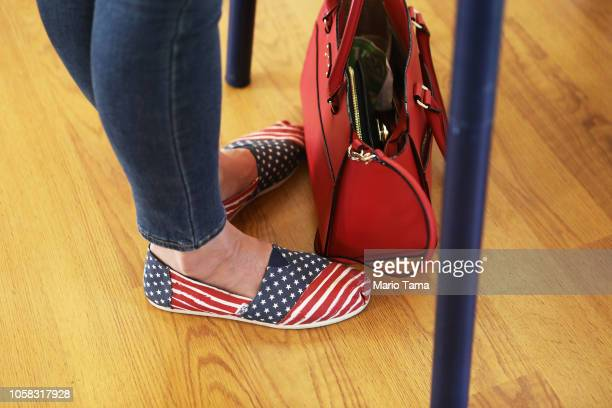 Democratic Congressional candidate Katie Hill stands filling out her ballot in American flag shoes at a polling place in California's 25th...