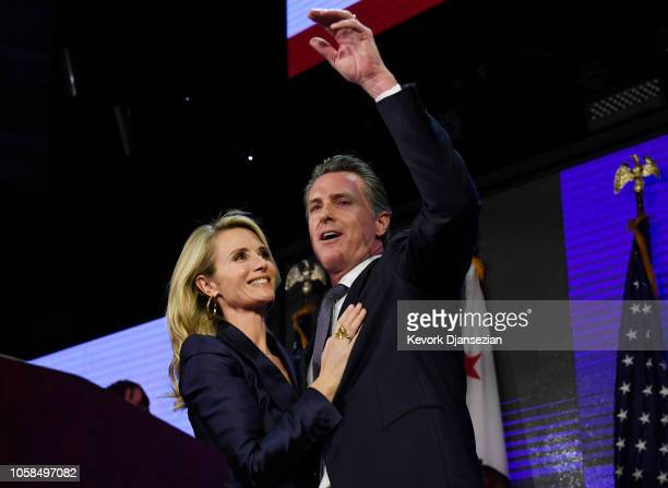 Democratic gubernatorial candidate Gavin Newsom and his wife Jennifer Siebel Newsom wave to supporters during election night event on November 6 2018...