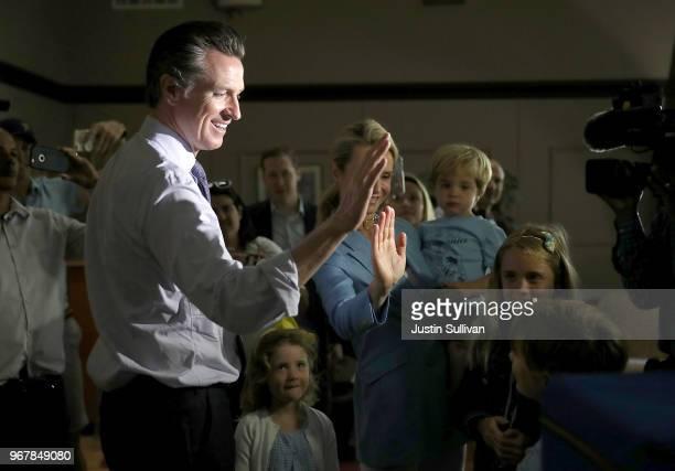 Democratic gubernatorial candidate Lt Gov Gavin Newsom and his wife Jennifer Siebel Newsom highfive with their kids after voting at the Masonic...