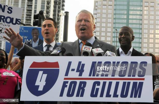 Democratic gubernatorial nominee Andrew Gillum and his running mate Chris King listen as Orlando Mayor Buddy Dyer speaks at a campaign event on...