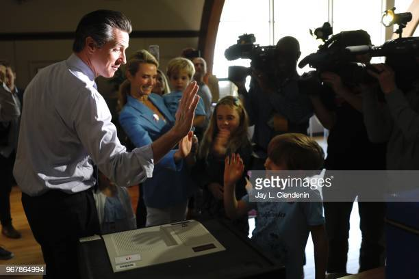 Democratic Lt Gov Gavin Newsom gets a highfive from his son Hunter after casting his ballot in the primary election with his wife Jennifer Siebel...