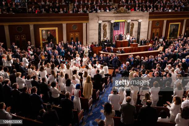 Democratic members celebrate in the House Chamber as President Donald Trump recognizes their achievement of electing a record number of women to...