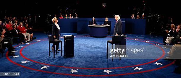 TOPSHOT Democratic nominee Hillary Clinton and Republican nominee Donald Trump arrive on stage during the second presidential debate at Washington...