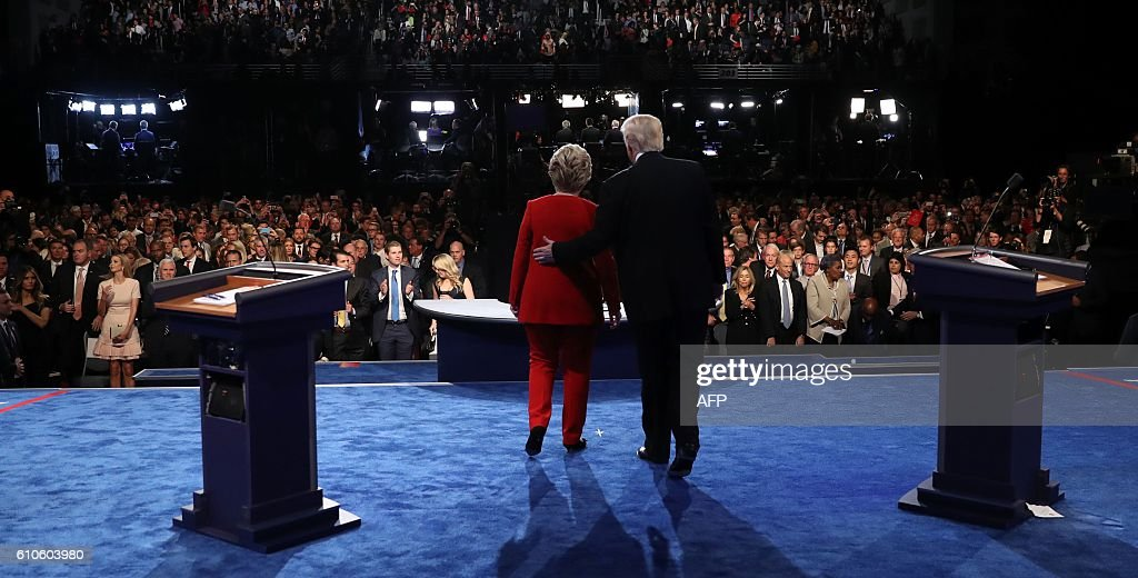 TOPSHOT - Democratic nominee Hillary Clinton (L) and Republican nominee Donald Trump greet the audience at the end of the first presidential debate at Hofstra University in Hempstead, New York on September 26, 2016. Hillary Clinton and Donald Trump face off in one of the most consequential presidential debates in modern US history with up to 100 million viewers set to tune in. / AFP / POOL / joe raedle