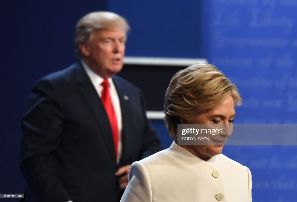 TOPSHOT - Democratic nominee Hillary Clinton (R) and Republican nominee Donald Trump walk off the stage after the final presidential debate at the Thomas & Mack Center on the campus of the University of Las Vegas in Las Vegas, Nevada on October 19, 2016. / AFP PHOTO / Robyn Beck