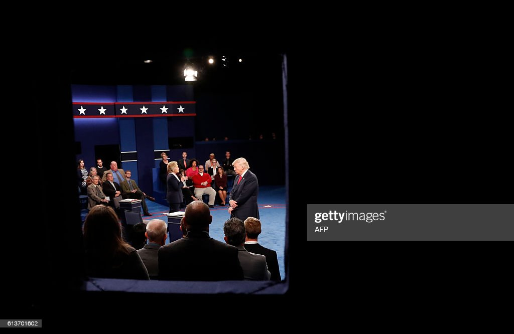 TOPSHOT - Democratic nominee Hillary Clinton (c) and Republican Presidential nominee Donald Trump (R) participate in a town hall debate at Washington University in St. Louis, Missouri, on October 9, 2016. / AFP / POOL / RICK