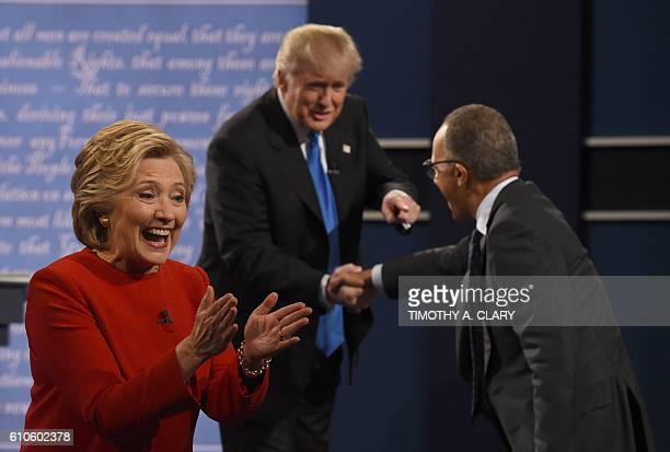 Democratic nominee Hillary Clinton reacts as Republican nominee Donald Trump shakes the hand of debate moderator Lester Holt after the first...
