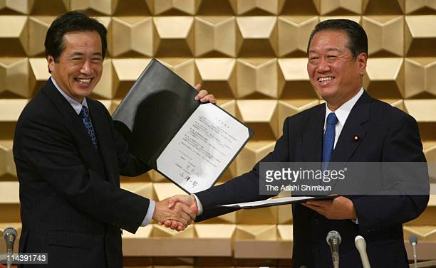 Democratic Party of Japan President Naoto Kan and Liberal Party President Ichiro Ozawa shake hands during the signing ceremony to merge at a hotel on...