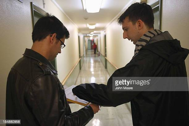 Democratic party volunteers Chris Lettero and Matt Lattanzi check apartment numbers while canvasing for votes October 28 2012 in Youngstown Ohio The...